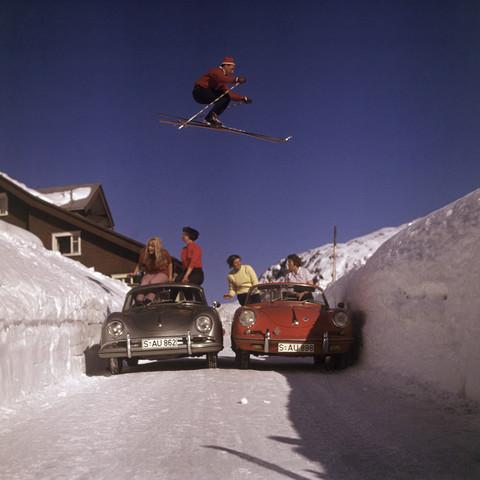 Ein Skifahrer ¸berspringt eine ausgefr‰ste Strafle  in den Kitzb¸hler Alpen. Die Wagen sind Porsche 356.